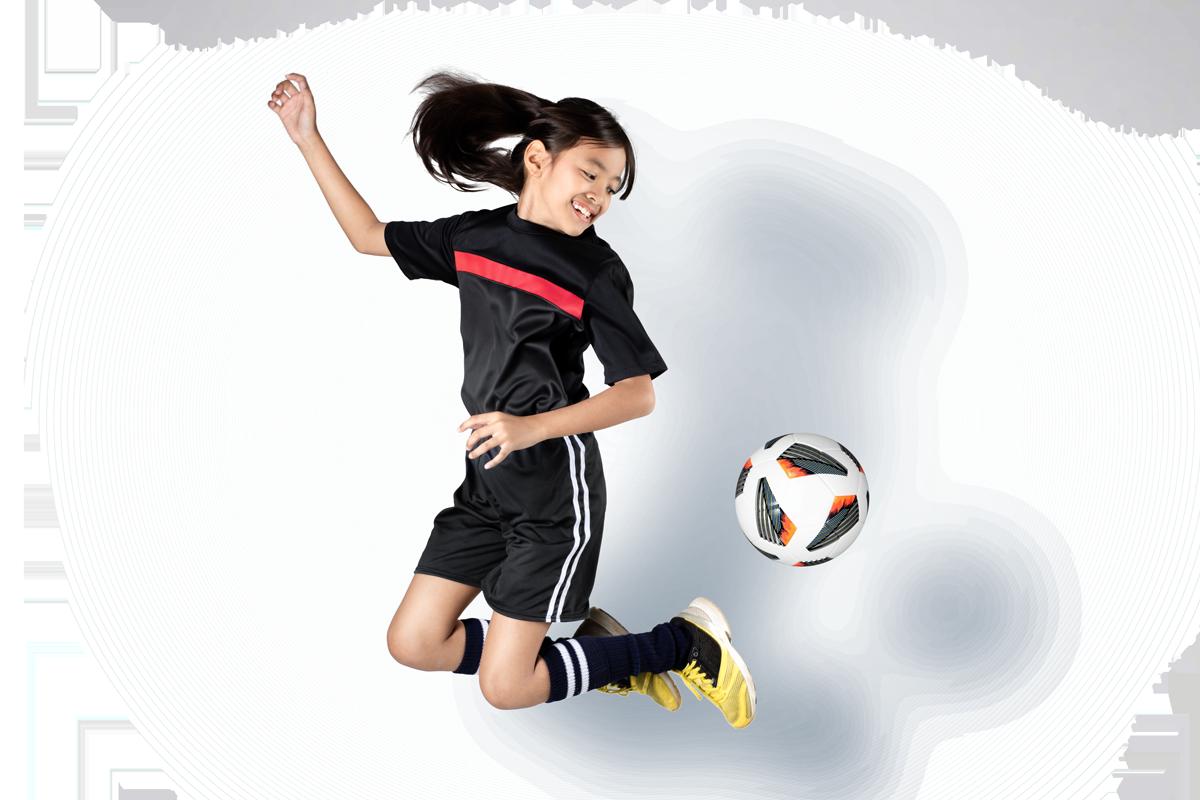 Tjej som hoppar och sparkar på fotboll
