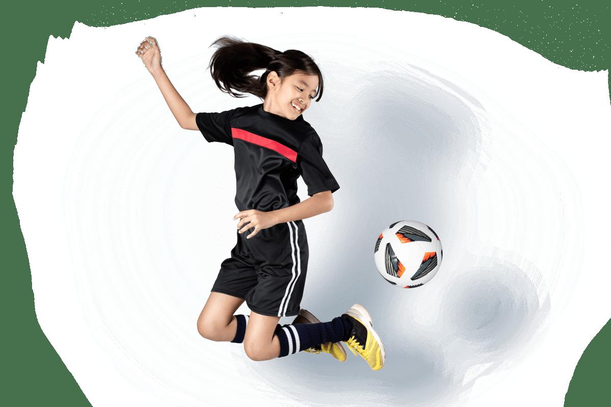 Tjej som hoppar och kickar en fotboll