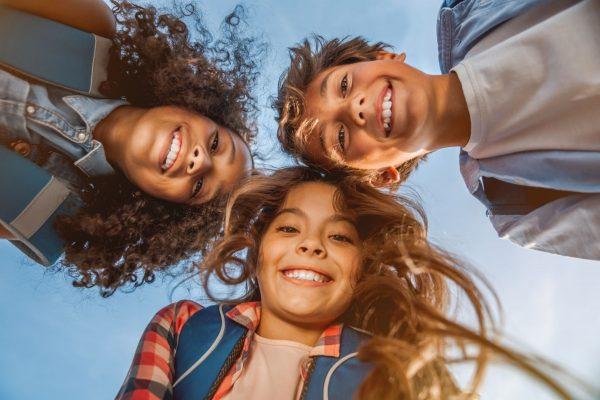 Tre glada barn som tittar in i kameran