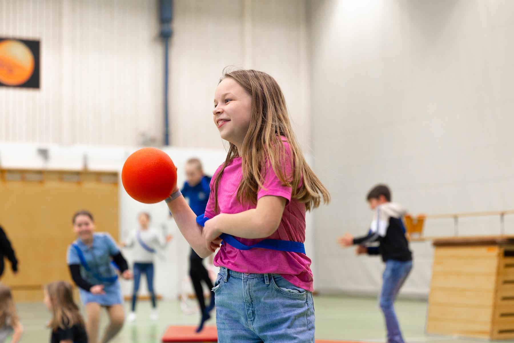 Elev spelar boll i gymnastiksal