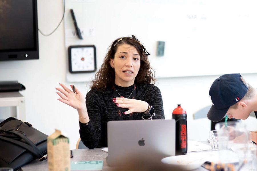 Kvinnlig lärare i klassrum som förklarar någonting framför en dator