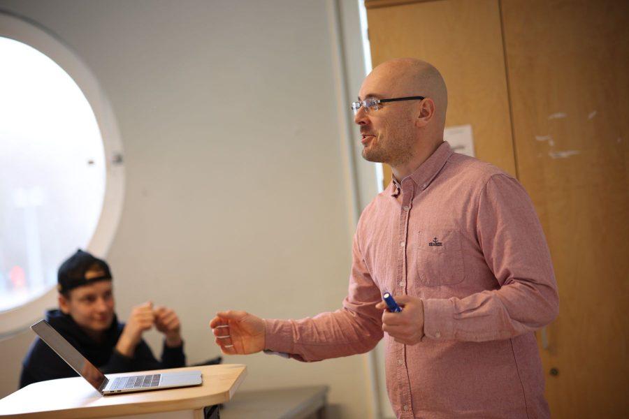 Manlig lärare som håller i en lektion i ett klassrum