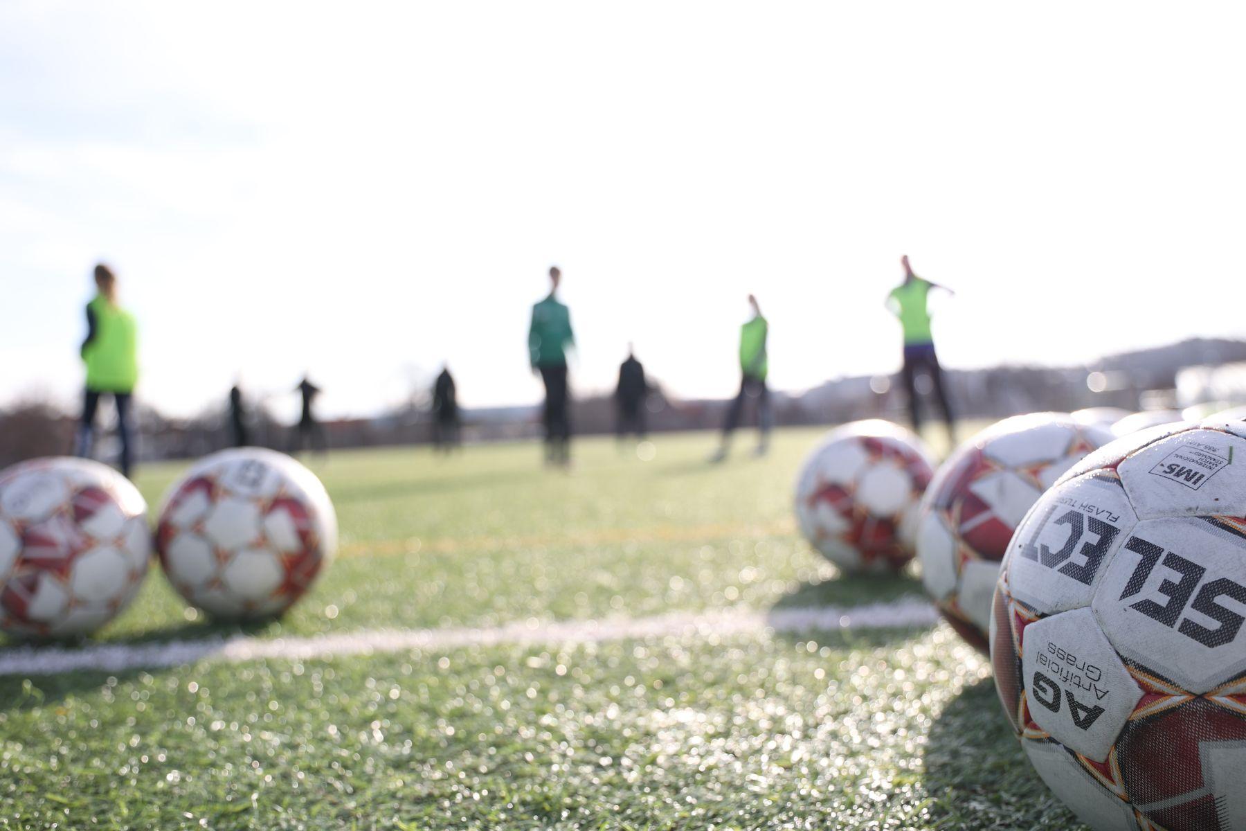 Forbollsplan med fotbollar i förgrunden