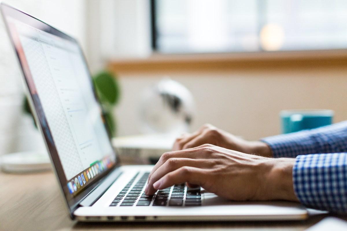 Närbild där någon skriver på laptop